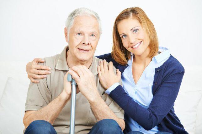 Lächelnde Frau mit einem glücklichen Senioren im Seniorenheim