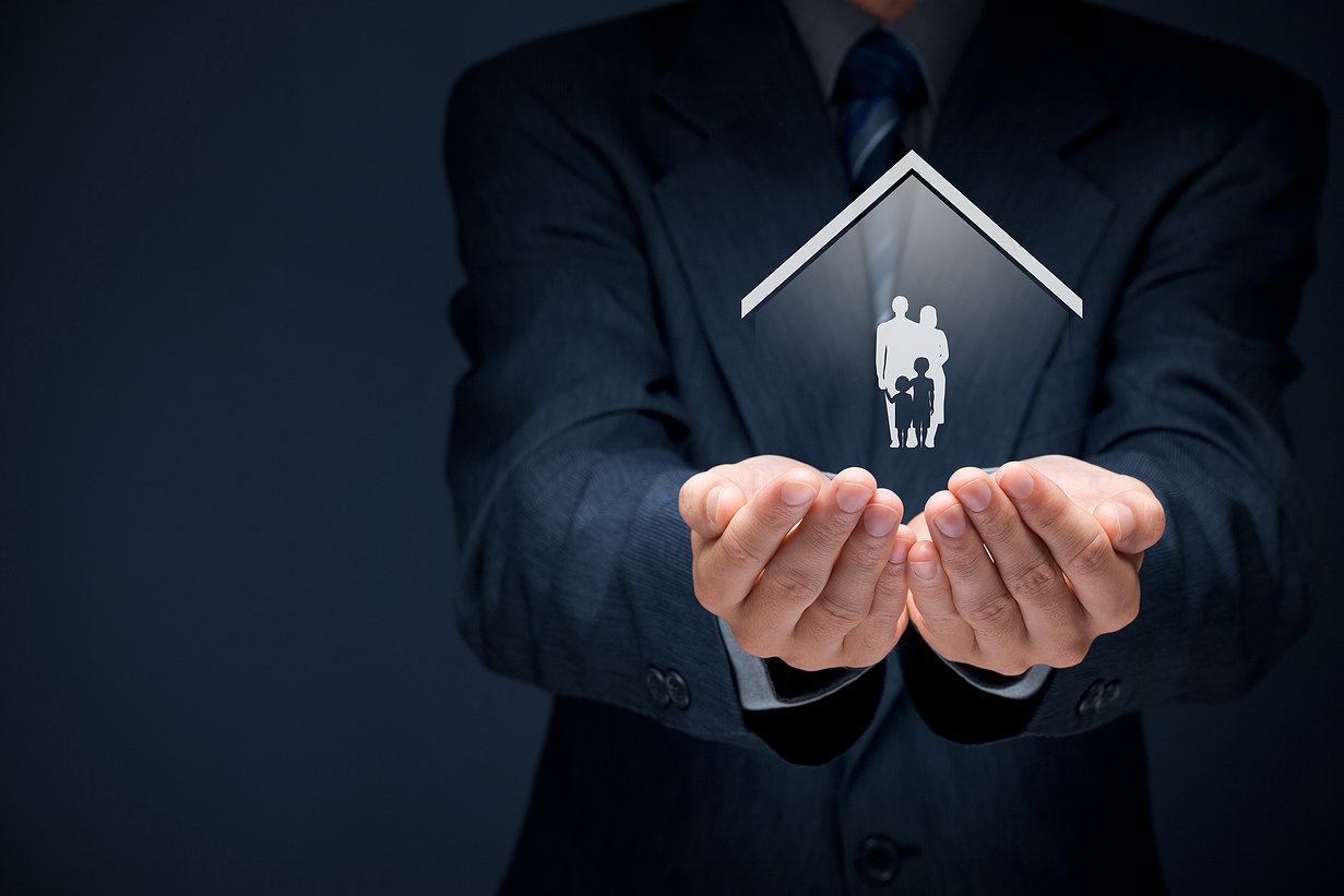 Insurance concept of family life and property insurance family services family policy and supporting families concepts. Businessman with protective gesture and silhouette representing young family and house.