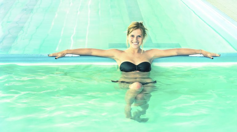 Beautiful woman in clear water looking at camera - Young girl swimming pool at exclusive resort - Medical concept of hydrotherapy spa treatment - Soft focus and natural light with bright vintage look
