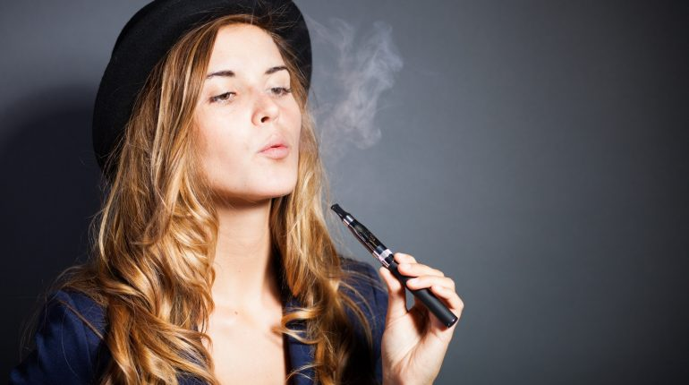 Elegant woman smoking e-cigarette with smoke, wearing suit and hat
