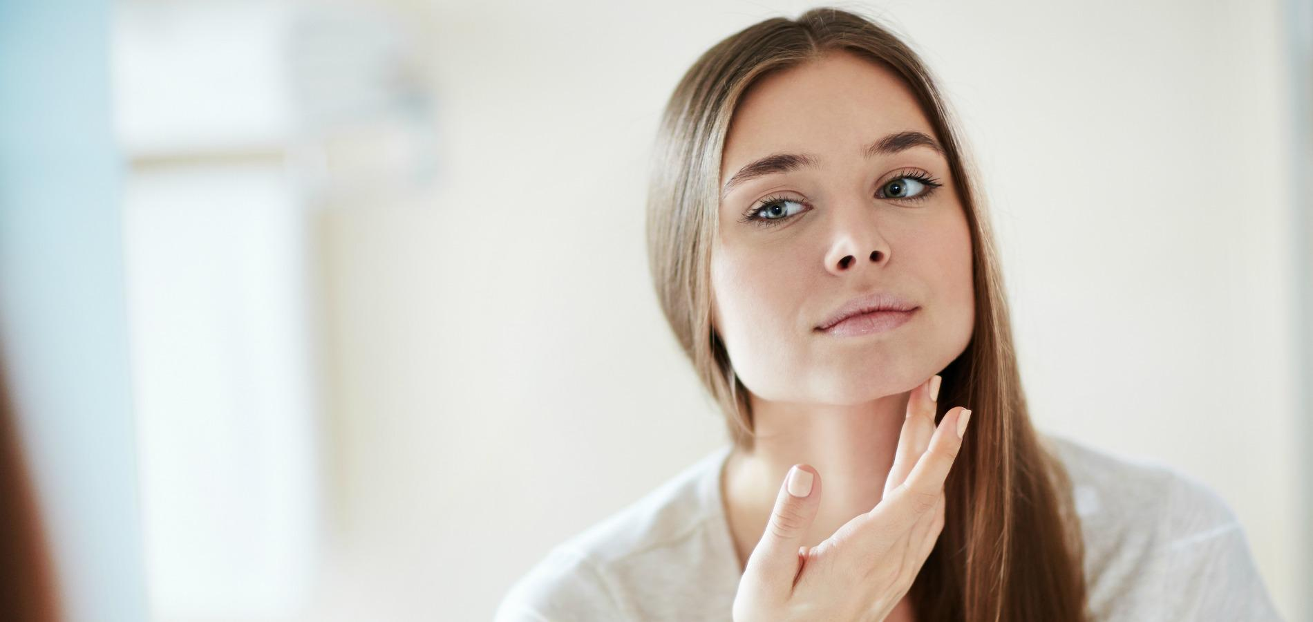 Young woman looking at mirror at home and applying cream on her face