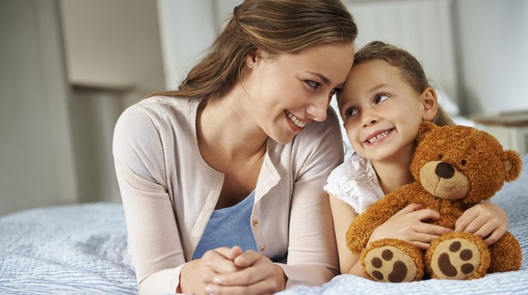 A little girl spending time with her mom while holding her teddy bear